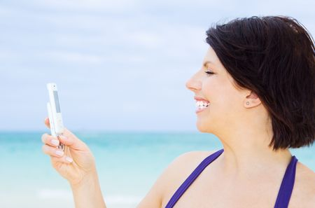 happy woman with white phone on the beach Stock Photo - 4405792