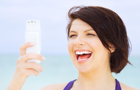 happy woman with white phone on the beach Stock Photo - 4413784