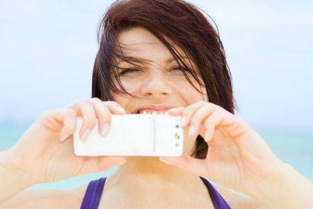 taking video: picture of happy woman using phone camera