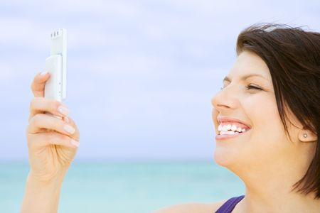 happy woman with white phone on the beach Stock Photo - 4421391