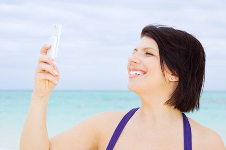 happy woman with white phone on the beach Stock Photo - 4439143