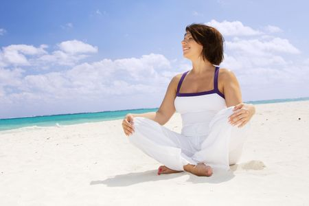 meditation of happy woman in lotus pose on the beach