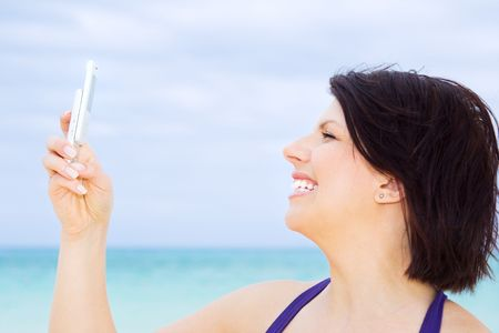 happy woman with white phone on the beach Stock Photo - 4439159