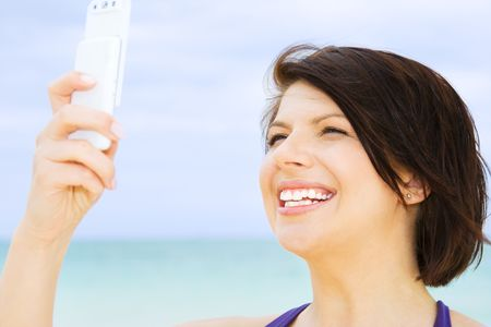 happy woman with white phone on the beach Stock Photo - 4439161