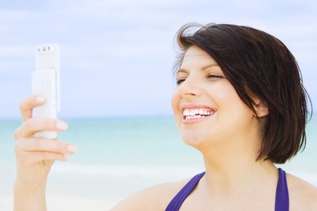 happy woman with white phone on the beach Stock Photo - 4451472