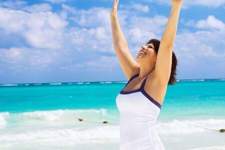 manos levantadas al cielo: mujer feliz con mano alzada en la playa LANG_EVOIMAGES