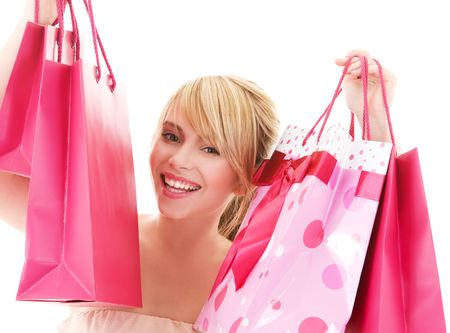 happy teenage girl with pink shopping bags