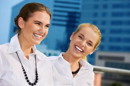 careless: two happy businesswomen in the city (focus on blonde) LANG_EVOIMAGES