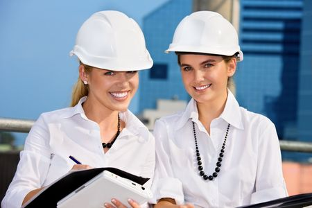 female contractors in a front of building site (focus on blonde) Stock Photo - 4584685