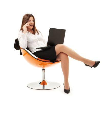 news online: businesswoman in chair with laptop and phone over white LANG_EVOIMAGES