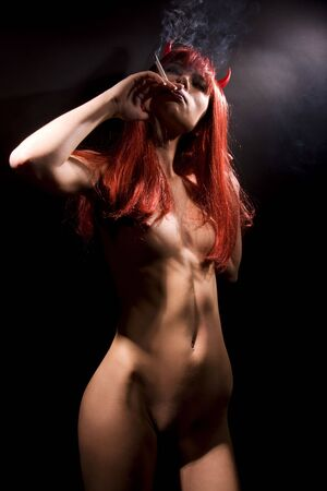 dark picture of smoking naked devil woman Stock Photo - 4606822