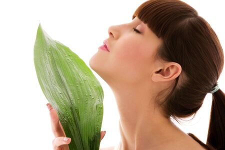 antiaging: picture of woman with green leaf over white