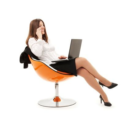 businesswoman in chair with laptop and phone over white Stock Photo - 4817122