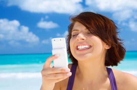 happy woman with white phone on the beach Stock Photo - 4827516