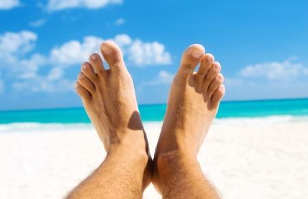 pies masculinos: imagen de los hombres en las piernas playa tropical de fondo