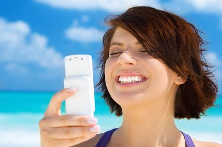 happy woman with white phone on the beach Stock Photo - 4900540