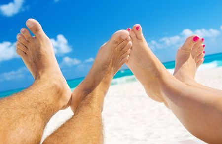 holiday: picture of male and female legs over tropical beach background