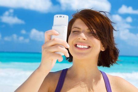 happy woman with white phone on the beach Stock Photo - 4946521