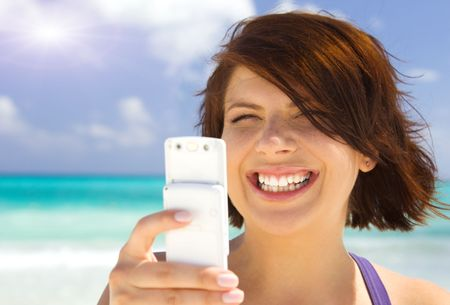 happy woman with white phone on the beach Stock Photo - 4977271