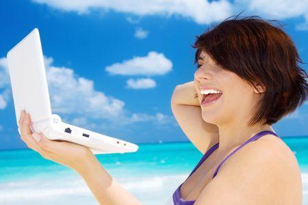 bella donna con computer portatile in spiaggia