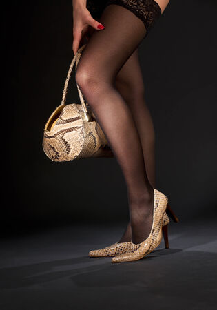 bodyscape: long legs in snakeskin shoes with handbag over black LANG_EVOIMAGES