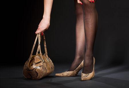 bodyscape: long legs in snakeskin shoes with handbag over black LANG_EVOIMAGES