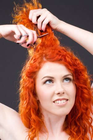 picture of lovely redhead with scissors over grey Stock Photo - 5197254