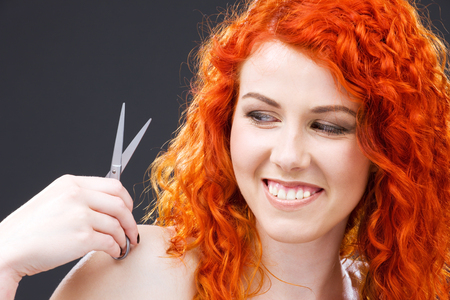 picture of lovely redhead with scissors over grey Stock Photo - 5197246
