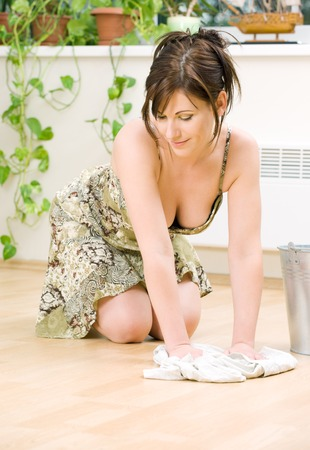 servant: bright picture of lovely housewife cleaning floor