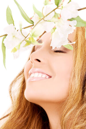 rejuvenating: picture of happy woman with white flowers (focus on smile) LANG_EVOIMAGES