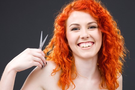 picture of lovely redhead with scissors over grey Stock Photo - 5197277