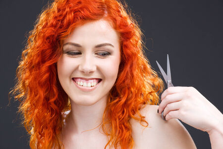 picture of lovely redhead with scissors over grey photo