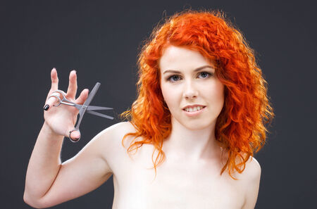 picture of lovely redhead with scissors over grey Stock Photo - 5348460