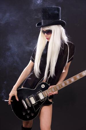 mujer en el sombrero de copa negro con guitarra el�ctrica y cigarrillos Foto de archivo - 5348562