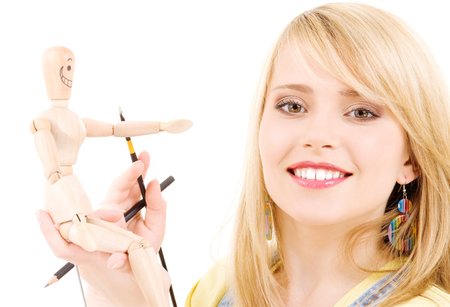 happy teenage girl with wooden model dummy over white Stock Photo - 5676955