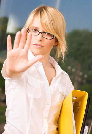 veto: bright picture of young woman making stop gesture LANG_EVOIMAGES
