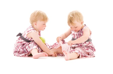 identical: picture of two adorable twins over white LANG_EVOIMAGES