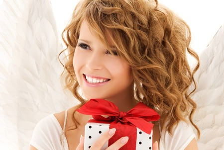 good heavens: picture of happy teenage angel girl with gift over white LANG_EVOIMAGES
