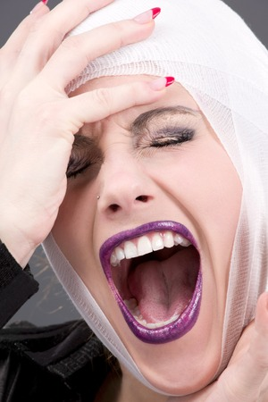 picture of screaming wounded woman face over grey Stock Photo - 5685116