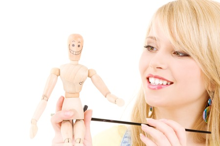happy teenage girl with wooden model dummy over white Stock Photo - 5676858
