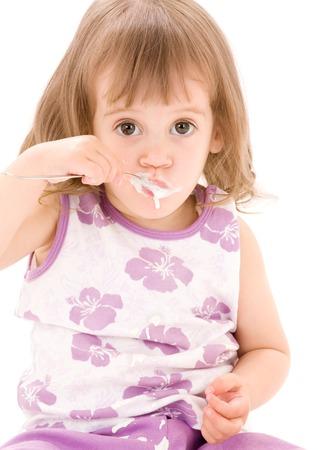 picture of little girl eating yogurt over white Stock Photo - 5685044