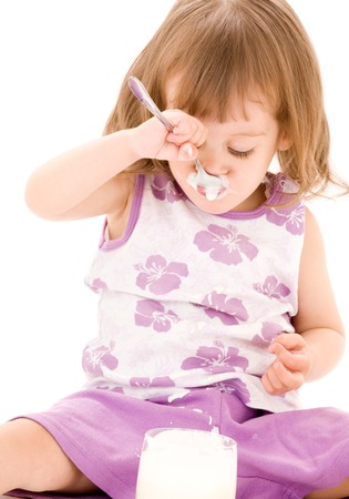 picture of little girl eating yoghurt over white Stock Photo - 5685052