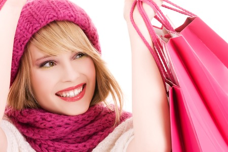 christmas shopper: happy teenage girl in hat with pink shopping bags