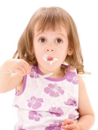 over eating: picture of little girl eating yogurt over white LANG_EVOIMAGES