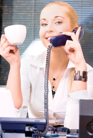 picture of lovely girl with phone and cup of coffee in office Stock Photo - 5676873