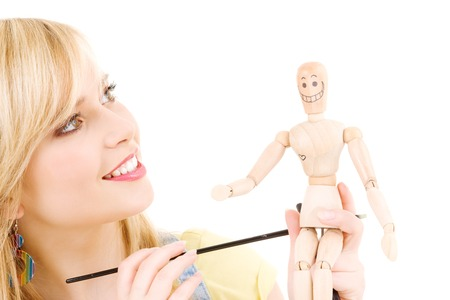 artists dummy: happy teenage girl with wooden model dummy over white