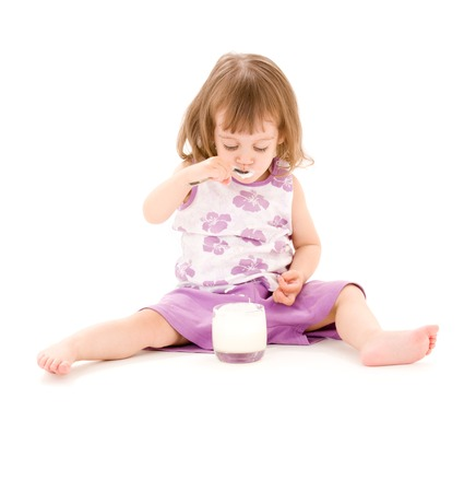 picture of little girl eating yogurt over white Stock Photo - 5668696
