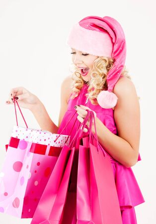 picture of cheerful santa helper girl with shopping bags photo
