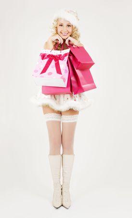 cheerful santa helper with pink shopping bags photo