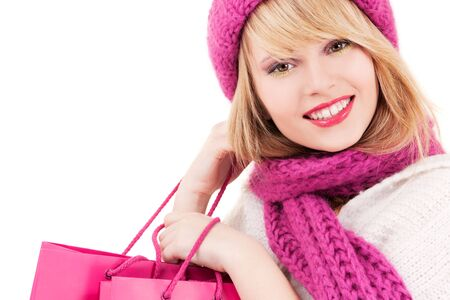 christmas shopping: happy teenage girl in hat with pink shopping bags
